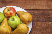apples and pears on rustic wood table