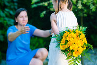 Happy mother's day! Child girl congratulates mom and gives her bouquet of yellow flowers - very shallow depth of field (focus on flowers)