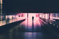 silhouette of a single person walking in    tunnel