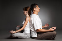 Healthy couple in yoga position on dark