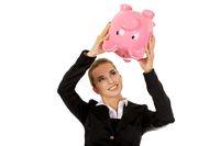 Young businesswoman saving money in piggybank