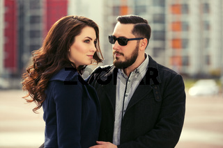 Young fashion couple in love walking on city street
