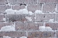 Frozen brick wall covered by hoarfrost