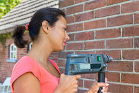 Woman holding drilling machine on brick wall