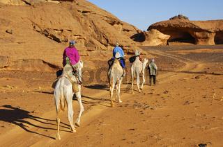 Touristen reiten auf Dromedaren in der Sahara