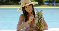 Sunbathing beauty drinks from a pineapple