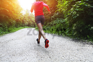 Young woman running on a countryside road
