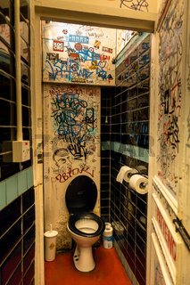 A toilet covered in grafitti inside a London pub