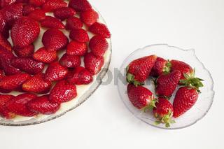 Erdbeertorte und Schuessel mit Erdbeeren