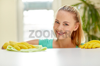 happy woman cleaning table at home