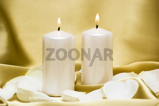 Candles with flower on golden background