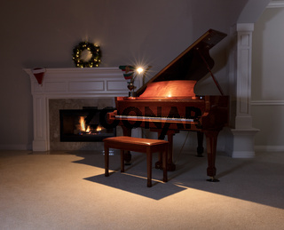 Piano with reading light and glowing fireplace during holiday season