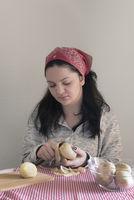 Brunette woman peeling potatoes
