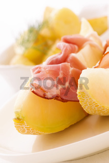Rock melon with gammon and potatos as closeup on a white plate