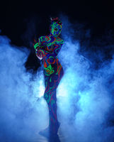 Girl with body art poses in UV light and smoke