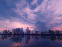 Picturesque view of the river with reflections of the trees of far riverbank. Dramatic evening scene under stormy clouds. Volga-river near Astrakhan, Russia