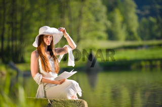 Long red hair romantic woman relax by lake with book