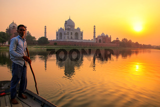 Local man steering boat on Yamuna river at sunset in front of Taj Mahal, Agra, India