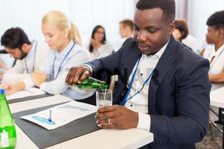 businessman drinking water at business conference