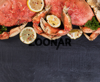 Freshly cooked crab with spices on natural dark slate stone