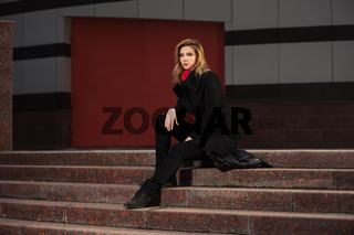 Fashion blond woman in black coat sitting on the steps
