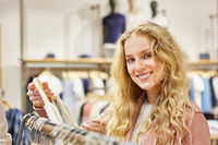 Lächelnde junge blonde Frau beim Shopping