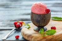 Cranberry ice cream ball in a wooden cup.