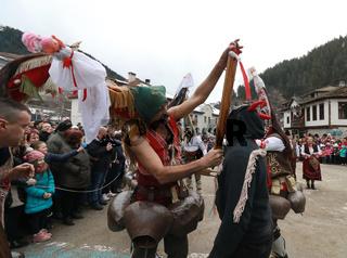 Shiroka laka, Bulgaria - March 4, 2018: People in in traditional Kukeri costume are seen at the Festival of the Masquerade Games 'Pesponedelnik' in Shiroka laka, Bulgaria.