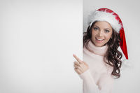 Woman in Santa's hat pointing at copyspace