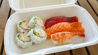 Delicious Sushi Variety in To Go Box on Table