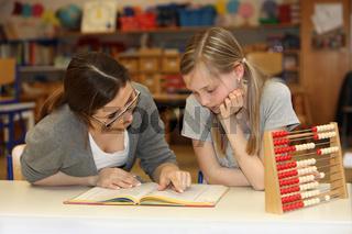 Lehrerin und Schülerin in der Schule mit Lehrbuch lernen gemeinsam -
