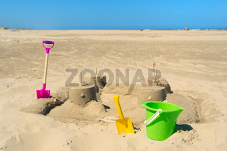 Sand castle with toys at the beach