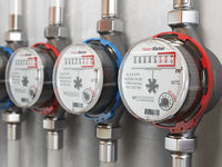 Row of water meters of cold and hot water on the wall background.
