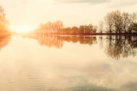 Foggy morning sunny landscape with trees and clouds reflections in river