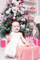 Christmas evening. Little girl sitting and unwraps gifts. white dress Princess