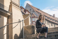 Woman sitting on stairs searching in a purse