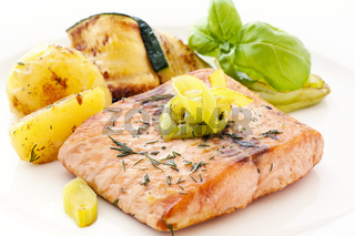 Salmon steak with roast potatoes and zucchini slices as closeup on white background