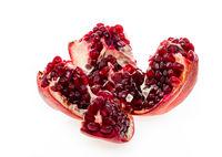 Open fresh ripe pomegranates on white isolated