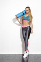 Sportswoman with gymnastic mat