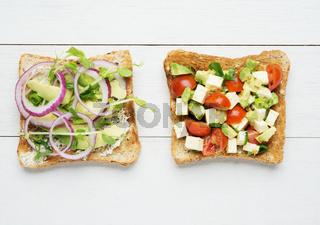 Two avocado toasts on white wooden background