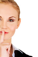 Business woman making silent sign with finger on lips