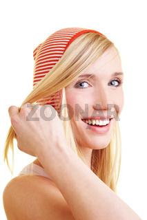 Lachende Frau streift Strähnen aus Gesicht