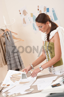 Female fashion designer working with sketches