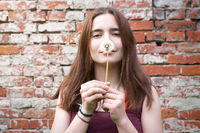portrait of a smiling young woman holding a dandelion