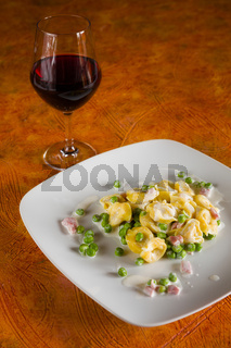 Tortellini with cream ham peas and red wine