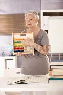 Senior teacher holding abacus