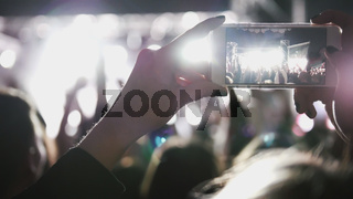 Spectators at the music concert shooting video on the smartphone