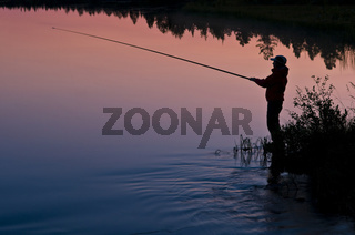 anglerin in abenddaemerung am see in lappland, schweden, female angler at sundwon at lake in swedish lapland