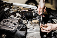 Automobile service worker or garage mechanic repairing auto car engine