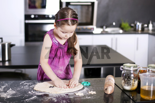 little daughter cooking in the kitchen
